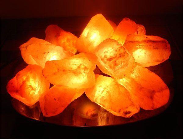 Соляная лампа Огненная Чаша из 15 камней на блюде, ионизатор воздуха, солевой светильник, ночник для снаСоляные лампы из камней<br>(Солевая) Соляная лампа Огненная Чаша из 15 камней на блюде<br> <br>Солевая лампа «Огненная Чаша» напоминает настоящие раскаленные угли костра, разложенных на зеркальной поверхности. Такое украшение отлично впишется в обстановку детской комнаты или спальни. При включении солевого светильника создается необычайно красивое и благородное освещение интерьера, благодаря электрической гирлянде с 15 лампочками-угольками, отражающимися в блестящей поверхности подставки. <br>  <br> <br>  <br> Этот прибор - не только простая настольная или детская лампа-ночник, а еще и бесшумно работающий лечебный ночник-ионизатор воздуха. Популярность пакистанские лампы из гималайской соли различных красных оттенков приобрели в первую очередь благодаря своим декоративным свойствам, но с их помощью можно также получить уникальный лечебный эффект. Красота добытой с глубины полкилометра пластов древнейшей каменной соли спасает и лечит людей. <br>  <br> <br>  <br> При работе плафон солевой лампа нагревается, и натрия хлорид насыщает воздух в комнате мельчайшей соляной аэрозолю, ионами, насыщенными отрицательным зарядом. Вдыхая такой состав воздуха, как после грозы, оказывается сильный оздоровительный эффект на человеческий организм. Особенно полезны такие «витаминные воздушные ванны» при большом количестве часто работающих электроприборов вокруг, при различных аллергических и легочных заболеваниях, а также при ослабленном иммунитете. <br>  <br> <br>  <br> Солевые светильники заслуженно пользуются популярностью и среди любителей стиля Феншуй. Купить солевую лампу в качестве подарка для создания гармонии и здоровой обстановки в комнате будет правильным решением. Солевая лампа упакована в красивую подарочную коробку.<br><br>Основные особенности соляной лампы Огненная Чаша<br> <br>Форма: чаша с камнями<br> <br>Цвет: пламя<br> <br>Вес: около 3 кг<br> <br>Подставка: керами