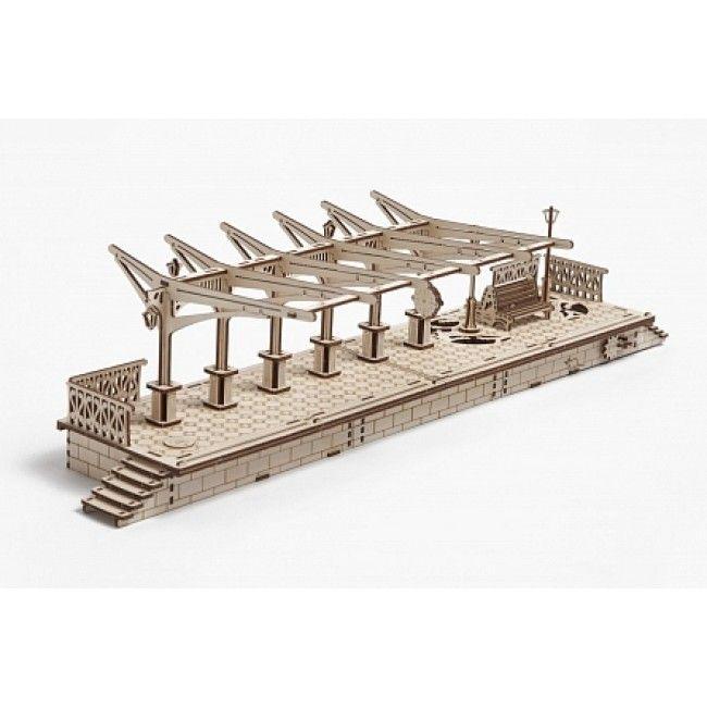 Деревянный конструктор UGEARS Перрон, (3D пазл), для детей, для взрослых, для конструированияДеревянный конструктор Ugears<br>Деревянный конструктор (3D пазл) UGEARS - Перрон<br> <br> <br>  <br>    <br>      <br>    <br>  <br>    Железнодорожный перрон с секретным ящиком для билетов - деревянная модель для самостоятельной сборки. Деревянный конструктор Перрон - это очередное произведение искусства, создать которое каждый может своими руками. В этой модели нет ничего лишнего, каждый элемент на своем месте. Настил Перрона имитирует мозаичную плитку, колоннада из шести столбов поддерживает изящную конструкцию козырька. На перроне красуется миниатюрная скамейка, которую, как бравые постовые, охраняет пара фонарей, а по бокам платформы ажурный, резной заборчик. Крошечные фонари, часы, ступеньки – все выполнено с удивительным мастерством и вниманием к деталям. Даже забавному коту, усевшемуся на «кирпичную» кладку основания перрона, и вездесущему голубю нашлось место.<br>  <br>    <br>      <br>    <br>  <br>    Если повернуть по часовой стрелке фонарный столб на правой оконечности перрона, выдвинется знак Stop. Левый фонарный столб, провернутый против часовой стрелки до упора, наглухо закроет потайной ящик. В этом положении, не зная секрета, открыть мини-хранилище нельзя даже ключом. Только повернув левый фонарный столб по часовой стрелке, ящик разблокируется и его можно будет открыть. Чтобы выдвинуть секретный ящик, нужно воспользоваться ключом, предварительно провернув его против движения часовой стрелки.<br>  <br> <br> <br> <br>   <br>    <br>   <br> <br> <br> <br>  Характеристики:<br> <br>  Материал: фанера<br> <br>  Размеры модели: 748х182х245 мм<br> <br>  Количество деталей: 196<br> <br>   <br>    <br>   <br> <br>  Для оптовых покупателей:<br> <br>  Чтобы купить деревянный конструктор Перрон оптом, необходимо связаться с нашими операторами по телефонам, указанным на сайте. Вы сможете получить значительную скидку от розничной цены в зависимости от объема заказа.<br> 